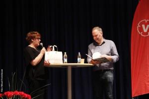 Rose-Marie Fältskog tackar Jonas Sjöstedt för framträdandet och överlämnar några lokalproducerade gåvor. Bland annat några ostar från Jürs mejeri, must från Skebokvarn och baklava från Sham Sweets.